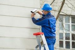 Tecnico maschio Standing On Stepladder che misura la macchina fotografica del CCTV Fotografia Stock