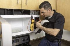 Tecnico Troubleshooting Microwave degli apparecchi Fotografie Stock
