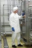 Tecnico in tute bianche e cappuccio che controllano processo industriale in pianta Fotografia Stock