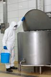 Tecnico in uniforme di bianco con il secchio che apre il carro armato di processo industriale Immagini Stock Libere da Diritti