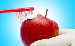 Tecnique di spazzolatura di dente con dentifricio in pasta e la mela rossa isolati Fotografie Stock