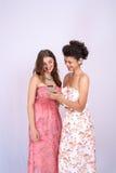 Tecnología, amistad y concepto de la gente - dos mujeres sonrientes de diversas razas con smartphones Imágenes de archivo libres de regalías