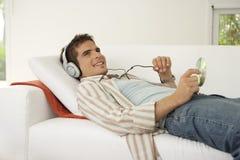 Tecnología casera en el sofá que escucha los auriculares Imagen de archivo