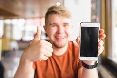 Tecnología, comunicación y concepto de la gente - hombre joven que muestra una pantalla elegante en blanco del teléfono con los p Fotos de archivo libres de regalías
