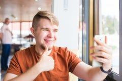 Tecnología, comunicación y concepto de la gente - hombre joven que sostiene un teléfono elegante con los pulgares para arriba Fotos de archivo