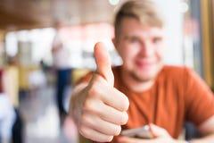 Tecnología, comunicación y concepto de la gente - hombre joven que sostiene un teléfono elegante con los pulgares para arriba Imagen de archivo libre de regalías