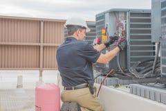 Tecnología de la HVAC que comprueba el condensador fotografía de archivo
