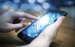 Tecnología digital conmovedora de la mano de la mujer joven en teléfono móvil imagen de archivo