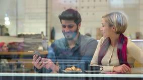 tecnología gente feliz con el teléfono móvil que se divierte en café metrajes
