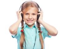 Tecnología, gente y concepto de la música - pequeña muchacha rubia con los auriculares aislados en el fondo blanco Foto de archivo libre de regalías