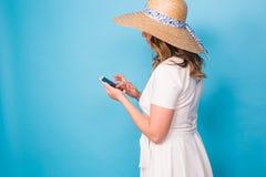 Tecnología, gente y concepto moderno de los dispositivos - escritura sonriente en teléfono, vista lateral de la mujer del mensaje Fotografía de archivo