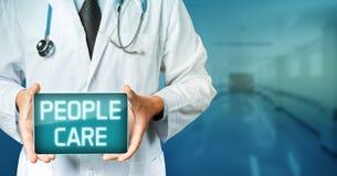 Tecnología global en concepto de la medicina Tableta del doctor Holding Blank Digital con el texto del cuidado de la gente imagen de archivo