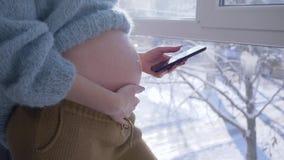 Tecnología móvil moderna para las mujeres embarazadas, hembra de maternidad con el abdomen grande con el teléfono inteligente con almacen de video