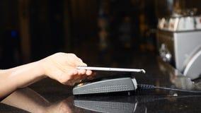 Tecnología moderna en forma de pago Pago sin contacto con Smartphone El pagar con un dispositivo del teléfono en una tarjeta de c almacen de metraje de vídeo