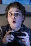 Tecnología. muchacho con la palanca de mando que juega al juego de ordenador en casa. Fotografía de archivo libre de regalías