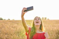 Tecnología, vacaciones de verano, vacaciones y concepto de la gente - mujer joven divertida que toma el selfie por smartphone en  Foto de archivo libre de regalías
