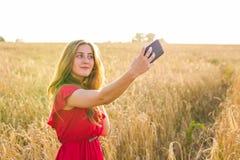 Tecnología, vacaciones de verano, vacaciones y concepto de la gente - mujer joven sonriente en el vestido rojo que toma el selfie Imágenes de archivo libres de regalías