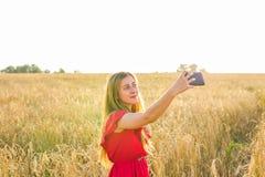 Tecnología, vacaciones de verano, vacaciones y concepto de la gente - mujer joven sonriente en el vestido rojo que toma el selfie Fotografía de archivo libre de regalías