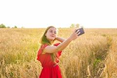 Tecnología, vacaciones de verano, vacaciones y concepto de la gente - mujer joven sonriente que toma el selfie por smartphone en  Fotos de archivo libres de regalías