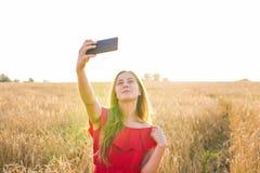 Tecnología, vacaciones de verano, vacaciones y concepto de la gente - mujer joven sonriente que toma el selfie por smartphone en  Imagenes de archivo