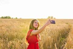 Tecnología, vacaciones de verano, vacaciones y concepto de la gente - mujer joven sonriente que toma el selfie por smartphone en  Fotos de archivo