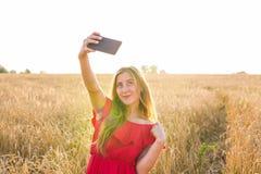 Tecnología, vacaciones de verano, vacaciones y concepto de la gente - mujer joven sonriente que toma el selfie por smartphone en  Imagen de archivo libre de regalías