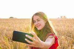 Tecnología, vacaciones de verano, vacaciones y concepto de la gente - mujer joven sonriente que toma el selfie por smartphone en  Foto de archivo libre de regalías