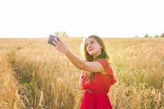 Tecnología, vacaciones de verano, vacaciones y concepto de la gente - mujer joven sonriente que toma el selfie por smartphone en  Imágenes de archivo libres de regalías