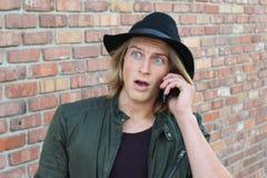 Tecnología y comunicación Hombre joven que habla en el teléfono celular móvil usando la expresión sorprendida smartphone de la ca Imagen de archivo