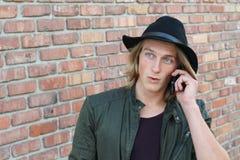 Tecnología y comunicación Hombre joven que habla en el teléfono celular móvil usando la expresión sorprendida smartphone de la ca Imagenes de archivo