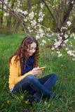 Tecnología y concepto de la gente - mujer joven sonriente con el smartphone que se sienta en hierba en parque Imagen de archivo