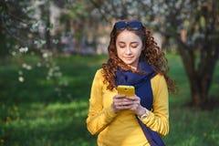 Tecnología y concepto de la gente - mujer joven sonriente que manda un SMS en smartphone Imágenes de archivo libres de regalías