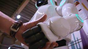 Tecnologías robóticas modernas Un hombre comunica con un robot, presiona un brazo mecánico plástico al robot, apretón de manos