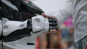 Tecnolog?as rob?ticas modernas Un hombre comunica con un robot, presiona un brazo mec?nico pl?stico al robot, apret?n de manos almacen de video