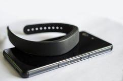 Tecnología usable de la banda elegante con el teléfono móvil Imagenes de archivo
