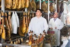 Tecnologi positivi felici della macelleria che controllano i giunti del iberico Fotografie Stock Libere da Diritti
