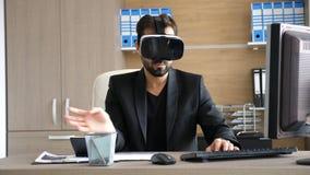 Tecnologia de VR - homem de negócios novo no escritório que veste auriculares da realidade virtual VR filme