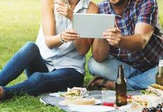 Tecnologia della compressa di Digital di rilassamento di unità di picnic della gente immagini stock libere da diritti