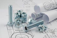 Tecnologia di ingegnere meccanico Dadi - e - bulloni sui disegni di carta immagine stock