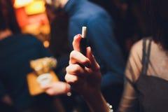 tecnologia do produto de cigarro da Calor-não-queimadura E-cigarro da terra arrendada da mulher em sua mão antes de fumar fotografia de stock royalty free