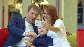 Tecnologia e concetto della gente - giovane coppia felice con i sacchetti della spesa e lo smartphone che prendono selfie in cent archivi video