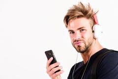 Tecnologia e musica l'uomo muscolare sexy ascolta audio uomo in cuffie isolate su bianco Libro elettronico ascolto non rasato del fotografia stock