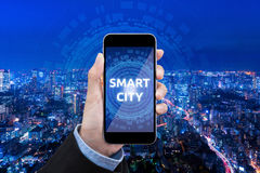 Tecnologia esperta da cidade da mostra da mulher de negócio no telefone celular imagens de stock