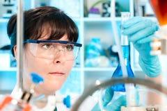 A tecnologia fêmea trabalha no laboratório químico Imagens de Stock