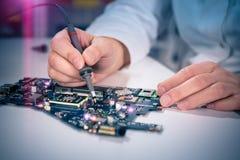 A tecnologia fixa o cartão-matriz no centro de serviço Foto de Stock Royalty Free