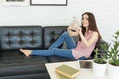 Tecnologia, fotografia e conceito dos povos - retrato da mulher bonita que toma os selfies que encontram-se no sofá escuro fotos de stock royalty free