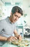 A tecnologia masculina energética nova fixa o dispositivo eletrónico Fotos de Stock Royalty Free