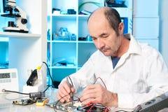 A tecnologia masculina superior repara a placa de circuito Fotografia de Stock Royalty Free
