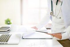 Tecnologia medica, fine su medico che legge un rapporto in compressa fotografia stock libera da diritti
