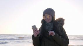 Tecnologia moderna, femminile in occhiali da sole che si siedono su Internet facendo uso del telefono cellulare stock footage